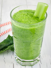 Green smoothie with celery, cucumber, spinach, apple and lemon on a white wooden table