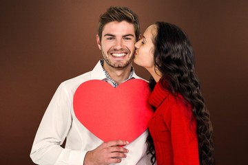 Composite image of man holding paper heart and being kissed