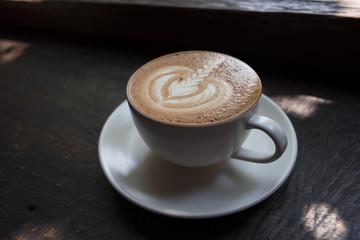 Latte art on cappuccino coffee on dark wood background