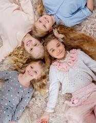 Group of beautiful little girls lying head to head on carpet.
