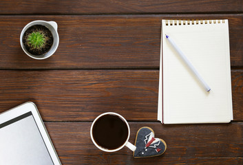cup of coffee, notepad and an electronic tablet on a wooden background, top view