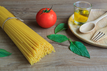 Spaghetti and tomatoes with basil on wooden table