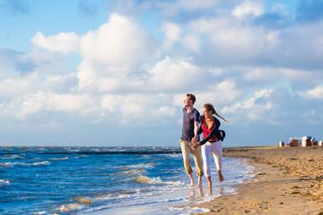 Paar genießt romantischen Sonnenuntergang am Nordsee Strand