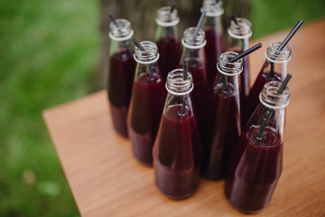 drink in bottles with a straw on a wooden table on a background