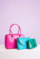 Three colorful leather bags and purses on the table. isolated on light purple color.