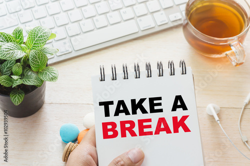 quot man holding take a break message on book and keyboard