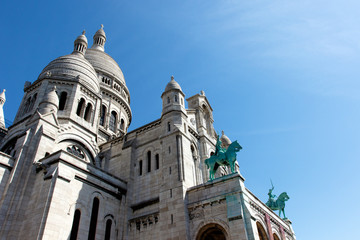 Color DSLR image of Basilica of the Sacre Couer on Montmartre, Paris, France with clear blue sky. Catholic church cathedral is popular Europe tourist destination. Vertical with copy space for text.