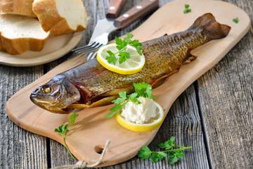 Geräucherte Forelle mit Meerrettich, Zitrone und Baguette rustikal serviert