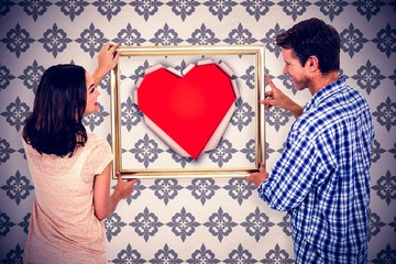 Composite image of happy couple holding picture frame