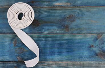 Material art background. Karate, Judo, TaeKwonDo belt on wooden table
