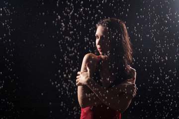 Woman in short red dress under water drops. Rain