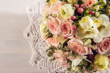 Beautiful wedding bouquet of roses and freesia on white wooden background, background for valentines or wedding day