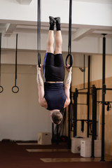 Caucasian athlete doing exercise on gymnastic rings