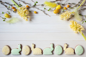 Easter wooden background with flowers hyacinth, willow twigs, eggs and feathers