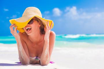 woman in bikini and straw hat having fun on tropical beach