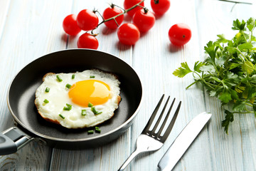 Fried eggs in pan on blue wooden table