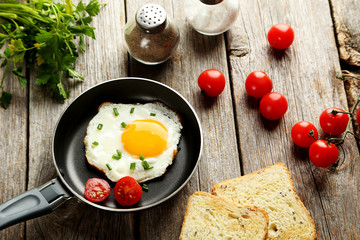 Fried eggs in pan on grey wooden table