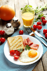 Fried eggs with bacon and toasts on plate on grey wooden table