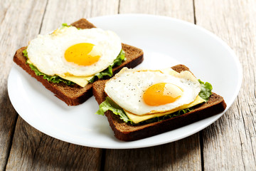 Fried eggs with toasts on plate on grey wooden table