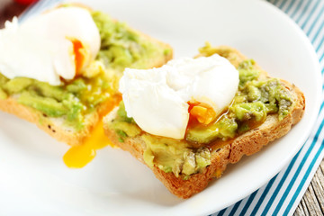 Poached eggs with avocado on toasts on grey wooden table