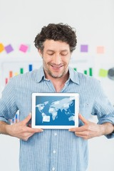 Composite image of smiling businessman showing digital tablet