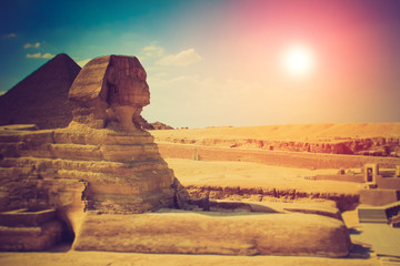 The full profile of the Great Sphinx with the pyramid in the background in Giza.