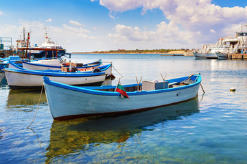 Seascape with a rowing boats. Bright sunny day. Boat Harbour. Several vintage rowboats against the backdrop of a calm sea surface and blue sky.