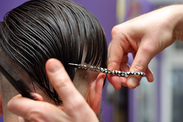 Barber cutting and modeling hair by scissors and comb
