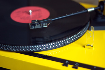 Turntable in yellow case playing a vinyl record with red label. Side view closeup