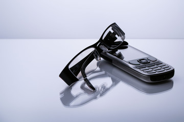 Old design cell phone with glasses lying on table