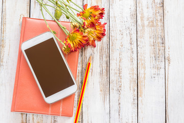 Fresh flower and smartphone on notebook on wooden table