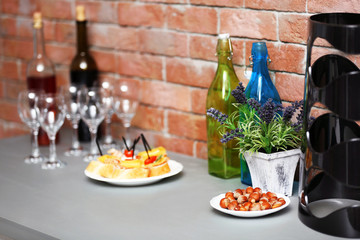Wine bottles and canape on the kitchen table against a brick wall