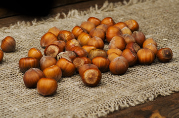 pile of hazelnuts in shell on wooden table