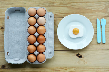 Flat lay of eggs tray beside a white plate with sunny side up eg