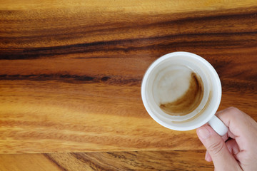 Hand holding a cup with coffee stain cup on wood background