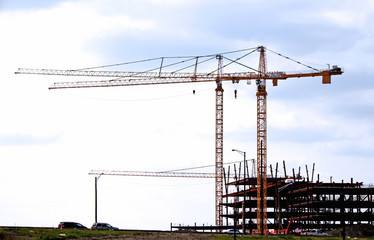 Construction site with red cranes on blue sky background