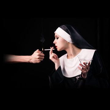 Smoking young nun with wineglass