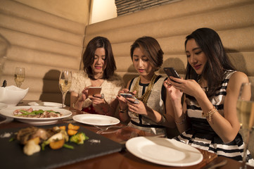 Three women are crazy about smart phone during a meal in the restaurant