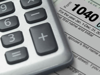 Photograph of a calculator and IRS 1040 form in close up.