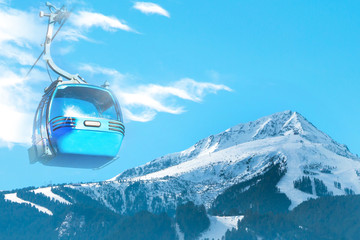 Vibrant travel ski resort background with cable car cabin, ski area, snow mountain peak, cloudy blue sky, copy space, place for text