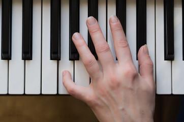 Woman hand playing piano music.