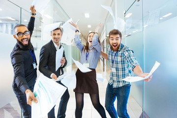 Group of joyful excited business people having fun in office Wall mural