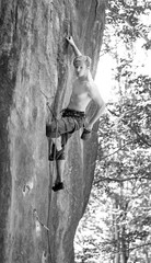 Young man rock-climbing on large boulder