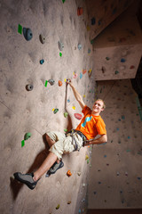 Young male climbing on practical wall in gym, bouldering