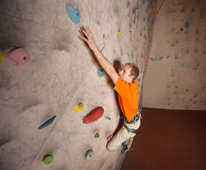 Young man climbing on practical wall in gym, reaches for next ha