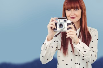 Composite image of hipster woman using old fashioned camera