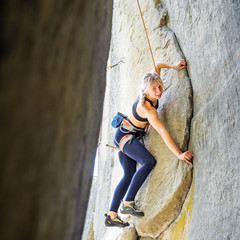 Obraz Strong pretty woman climbing steep stone wall in nature, with ro - fototapety do salonu
