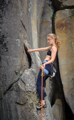 Young athletic girl climber climbing with rope and carbines on a