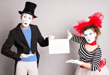 Two mimes   with a sign for advertising, April Fools Day concept