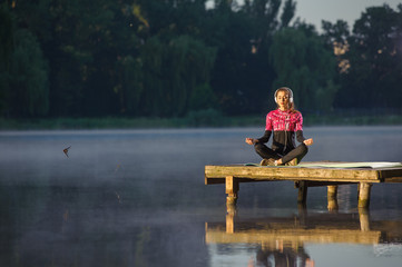young woman meditating in nature on the river